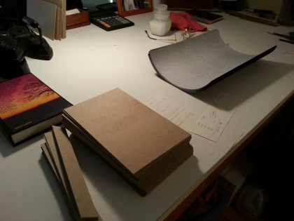 Making the covers. Note the stack of cut boards, the stack of cut pieces of book cloth.